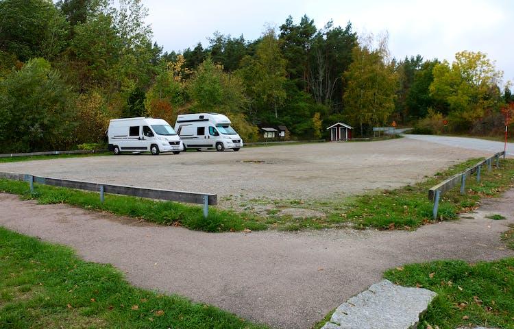 Två husbilar står på en stor grusad parkeringsyta. På håll ett dass och informationstavlor.