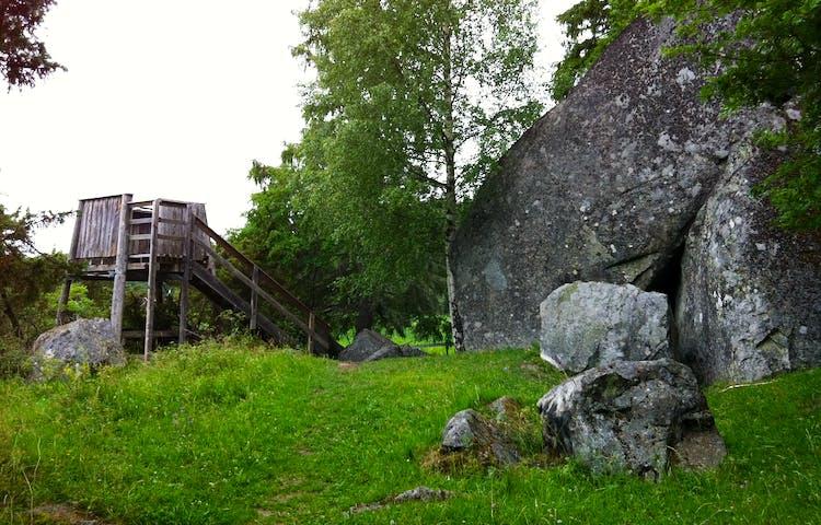 Ett litet fågeltorn står bredvid en gräsklädd stig och en stor stenbumling. En trappa leder upp till tornets plattform.