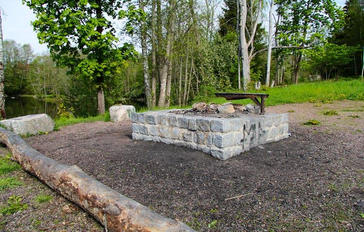 Murad eldstad med stockar och stenar runt som man kan sitta på.