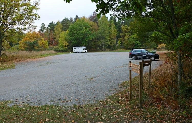 En husbil och en svart suv står parkerade en bit ifrån varandra på en fotbollsplansstor grusad yta.