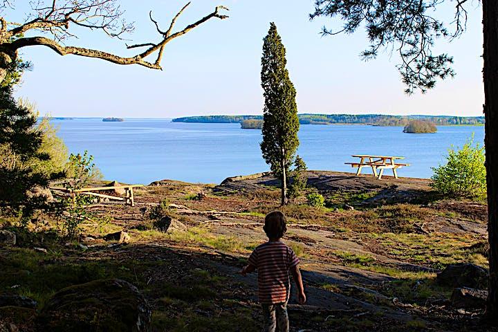 Ett barn går ut mot ett par bänkbord som står på höga klippor.