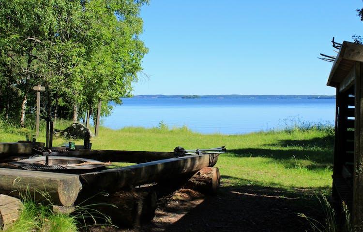 En låg grillplats med sittbänkar runtom står på en gräsyta vid vattnet.