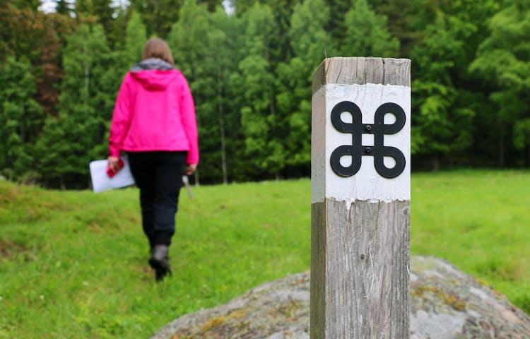 Vitmålad stolpe med en svart kringla som är symbolen för fornminne. På gräsmark går en person bortåt mot skogen.