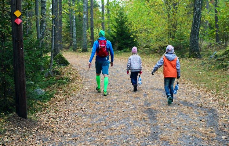 En person och två barn går bortåt på en grusväg. Orange och röda skyltar på stolpe.