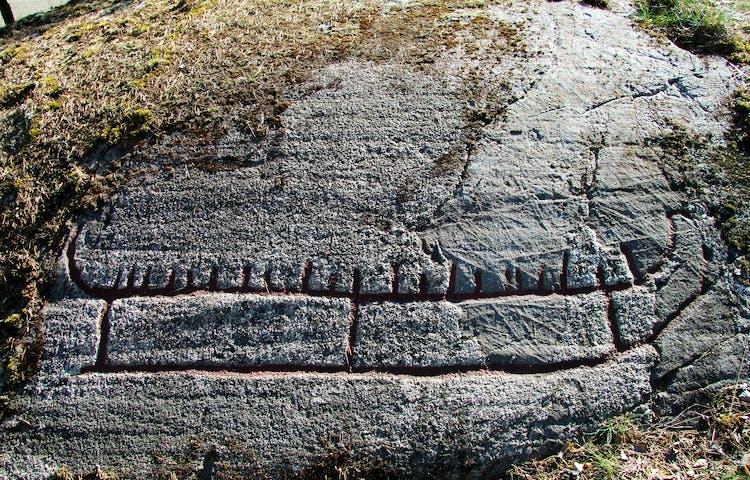 På klipphällen finns ett stort skepp, fotat framifrån. Ristningen visar en förenklad bild av hur en riktig båt kunde se ut för 2300 år sedan.