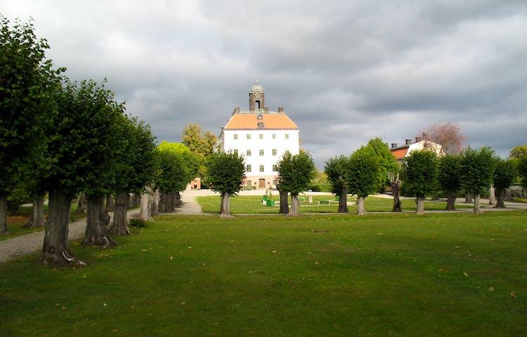 Ängsö slott med slottsträdgården framför. Himlen är grå men på det vita slottet skiner solen.