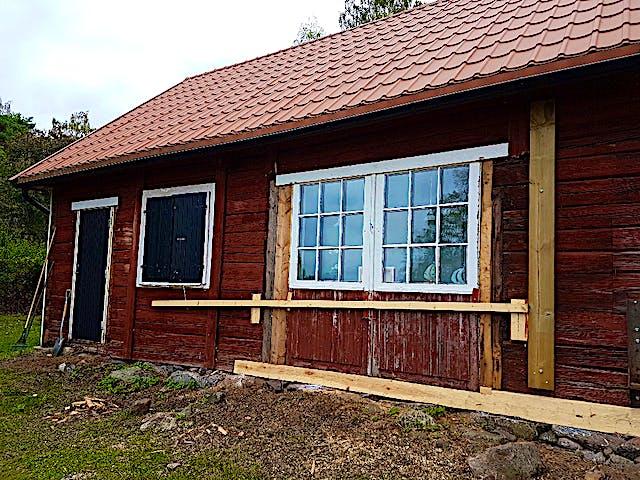 Röd liten träbyggnad med vita fönsterfoder. Vissa brädor i fasaden är omålade. Långsidan har tre fönster och en dörr längst till vänster.