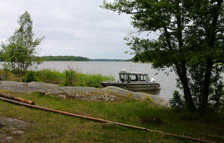En båt ligger förtöjd intill en klippa.