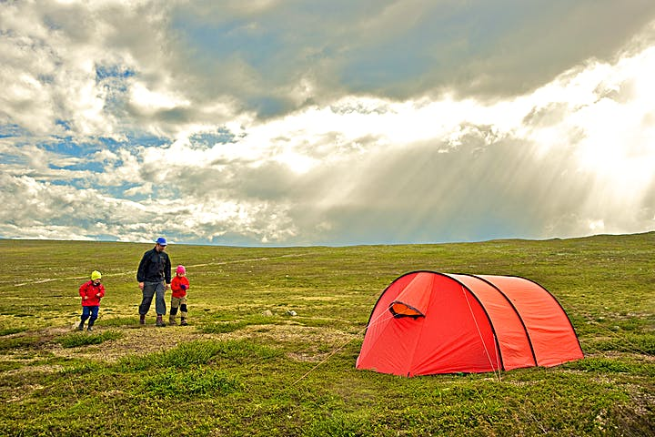 Bild på ett tält med en familj