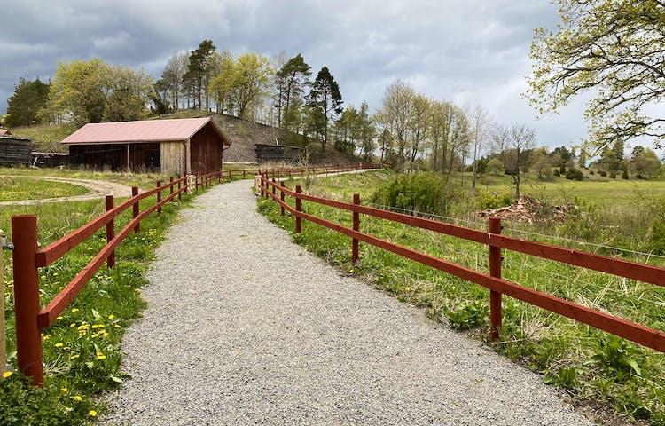 Mellan två trästaket går en bred grusväg. På ena sidan av vägen är det hagmarker och på andra sidan står en äldre lada av trä.