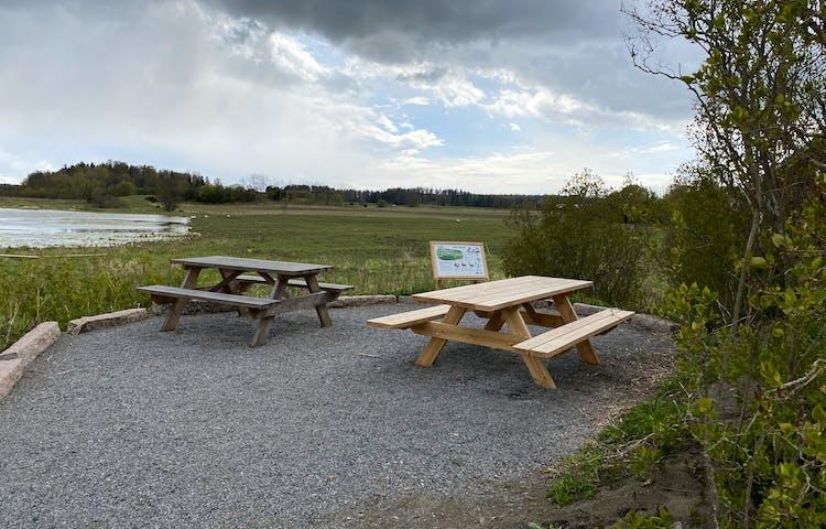 På en bred grusplan står två bänkbord. Det är gott om plats mellan borden. Runt kanterna av rastplatsen ligger större stenar.