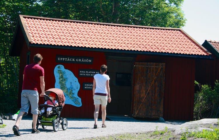Två vuxna går längst en grusväg mot en öppen bod. En av vuxna rullar ett barnvag med ett barn i.