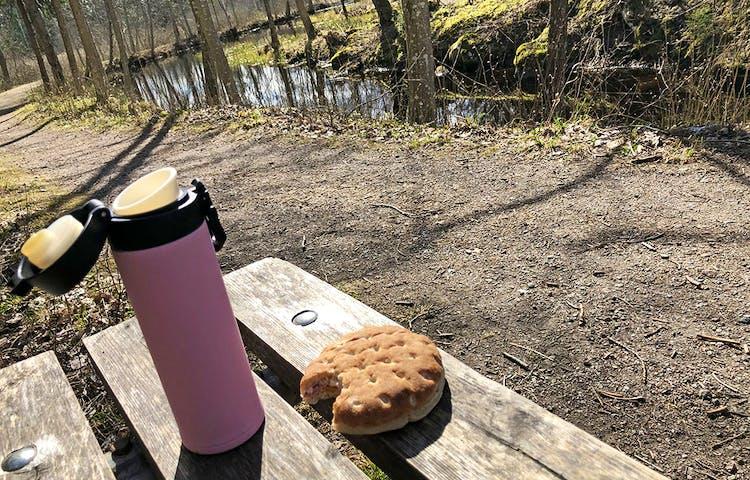 Rosa lite termos och dubbelsmörgås på en bänk i vårsol.