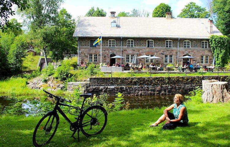 Katarina sitter i gräset bredvid sin cykel vid Kungskvaren i Borgvik