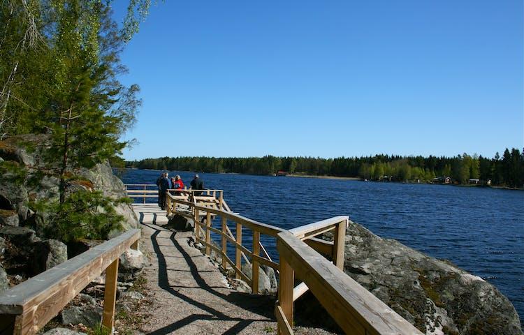 En grusad stig med handräcken på båda sidorna leder fram till en brygga vid vattnet. På bryggan står flera personer och tittar ut över vattnet.