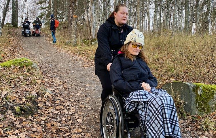 Bilden tagen nerifrån upp mot brant backe. En person i rullstol+ ledsagare. Långt upp i backen 2 personer i elrullstol.