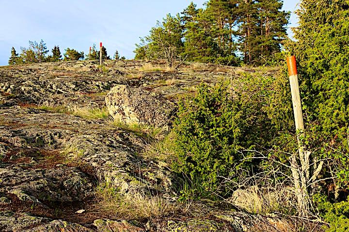Leden går över klippor. Längs leden finns stolpar med orange markering på toppen.