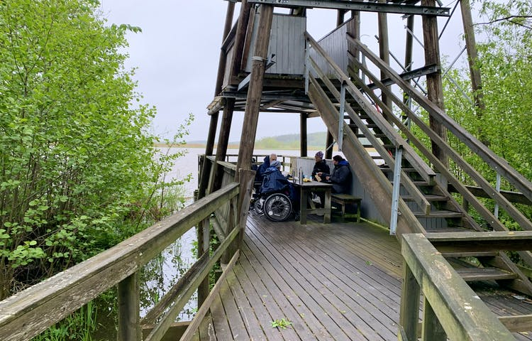 Fågeltorn med tillgängligt nedre plan och ett rastbord där några personer i rullstol fikar.
