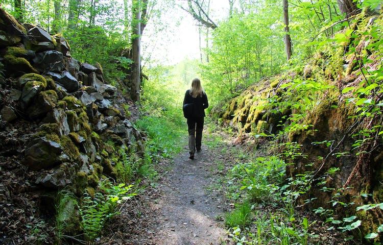 En person går på en stig mellan stenpartier.