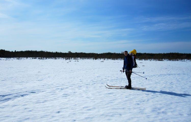 En person åker längdskidor på snötäckt mark.