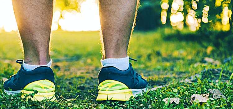 Närbild på två fötter i löparskor, som står på en gräsmatta.