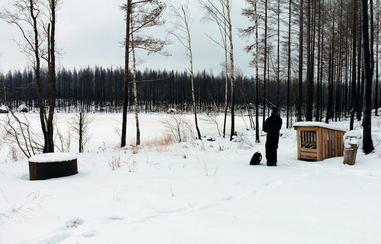 En svartklädd person står vid grillplats och vedförråd vid en snötäckt sjö.