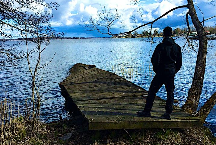 En person står i början av en träbrygga som går ut i Mälaren.