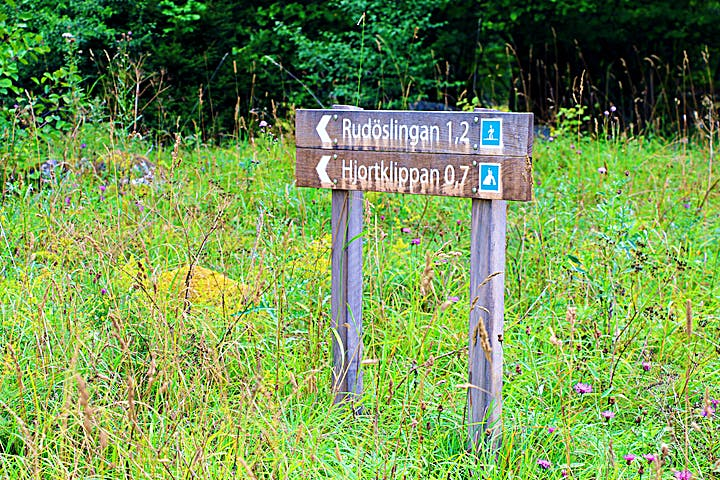 Träskyltar visar vägen mot Rudöslingan och Hjortklippan.