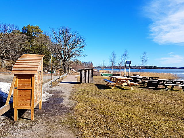 Ett manshögt träskåp står mellan en parkeringsplats och en rastplats. rastplatsen har pickninkbänkar.