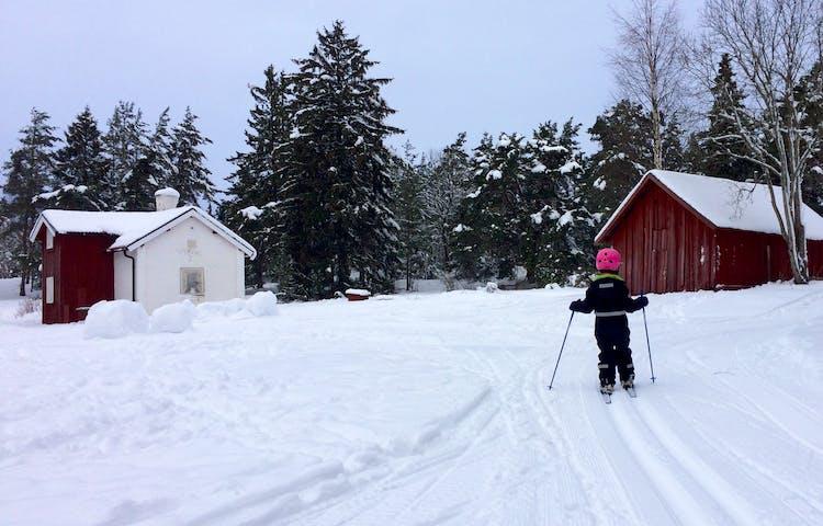 Ett barn åker skidor i ett spår mellan två hus.