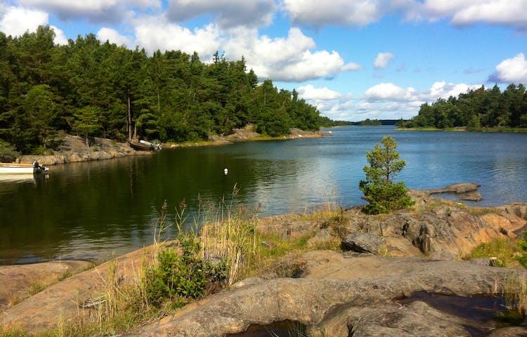 En havsvik med stenhällar och skog. Två mindre båtar är förankrade vid vattnet.