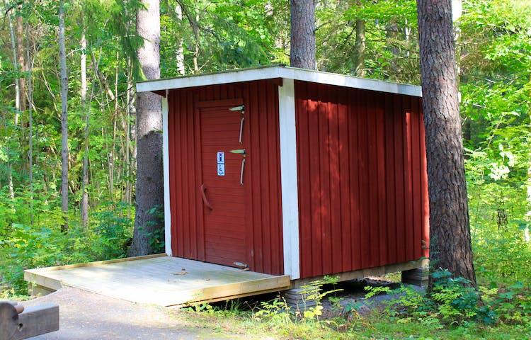 En tillgänglighetsanpassad torrtoalett med en bred träramp med kanter framför.