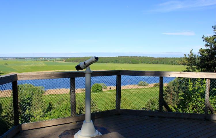 På en utsiktsplattform med skyddsräcke runtom står en kikare monterad på en stolpe. Framför kikaren står en låg träpall.