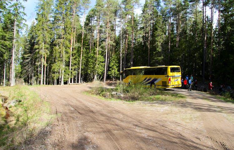 Enparkerad gul buss med människor som rör sig utanför.