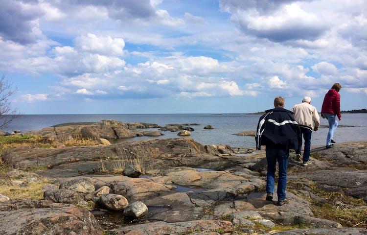 En kvinna och två män går efter varandra på en ojämn klipphäll vid havet.