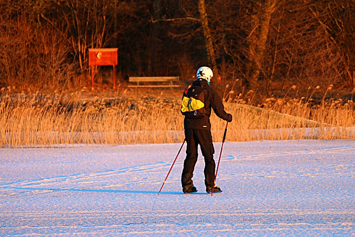 En person åker skridskor på isen med stavar.