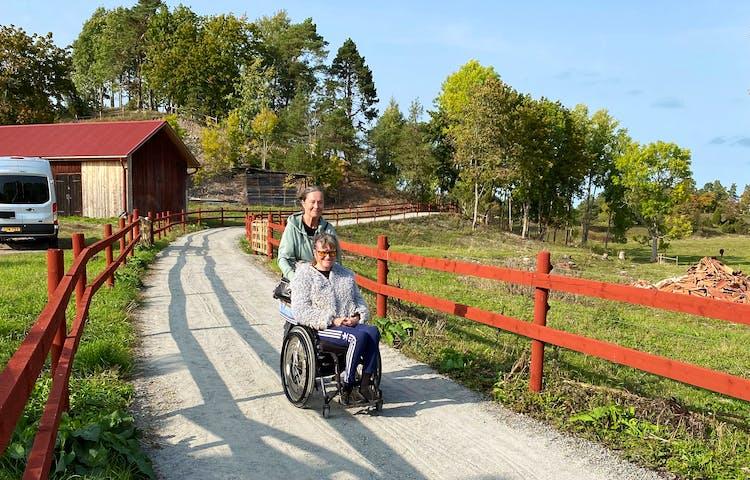 En kvinna skjutsar en man som sitter i rullstol längs en bred grusväg mellan två staket.