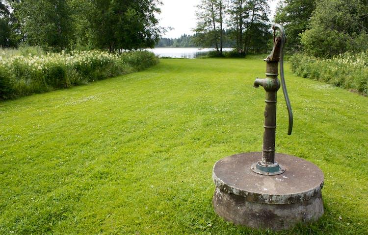 En gammaldags brunn med pump står på en välklippt gräsmatta. Gräsmattan leder till vattnet.