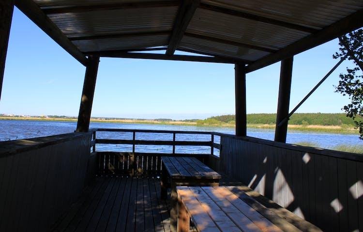 På fågeltornets andra våning står två bord och en lång bänk. Det är höga skyddsräcken runt och ett tak över.
