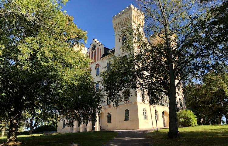 Bogesunds Slott bakom lövträd.