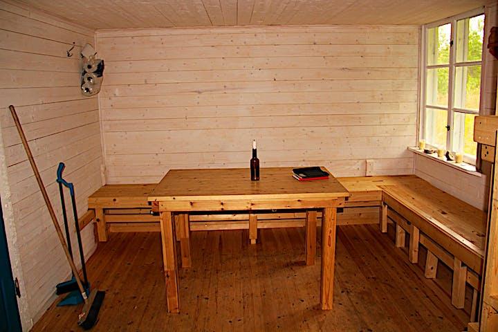 Insidan av stugan med väggfasta bänkar och ett bord.