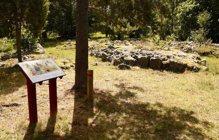 På ojämn hagmark står många träd och stora stenar. Vid ett av träden finns en informationsskylt.