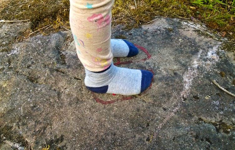 Två strumpklädda fötter står i en hällristning.
