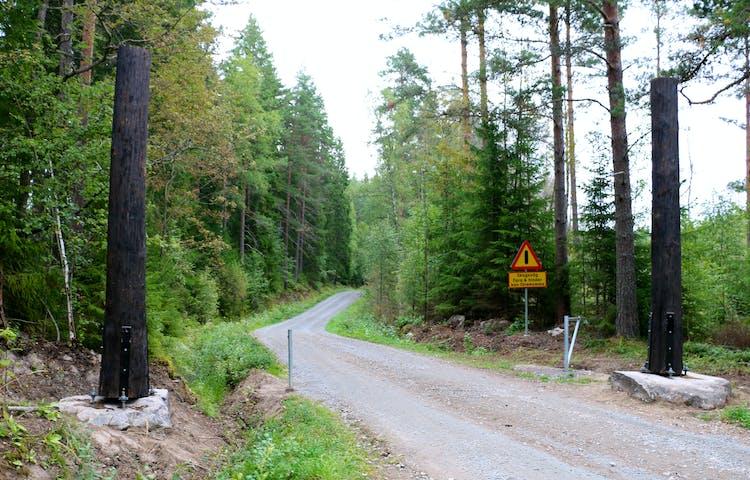 Grusväg som leder in i skogen. Vid infarten finns en vägbom och en varningsskylt.