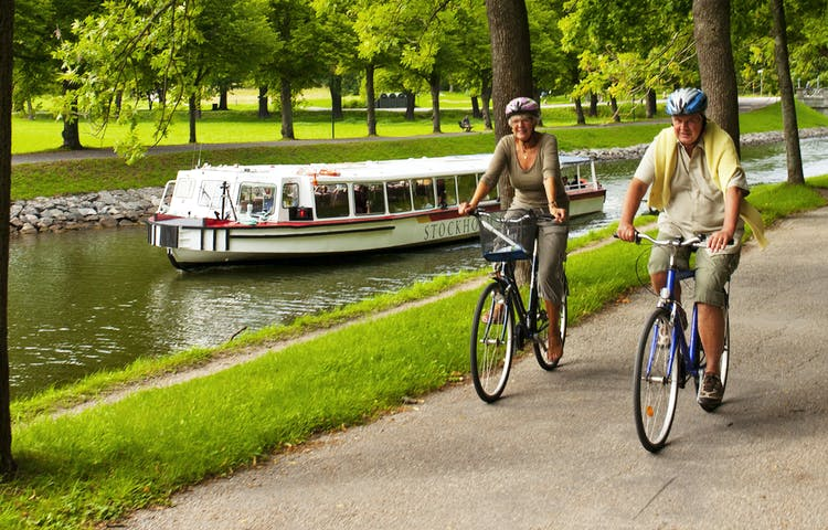 Båt och par som cyklar vid Djurgårdsbrunnskanalen.