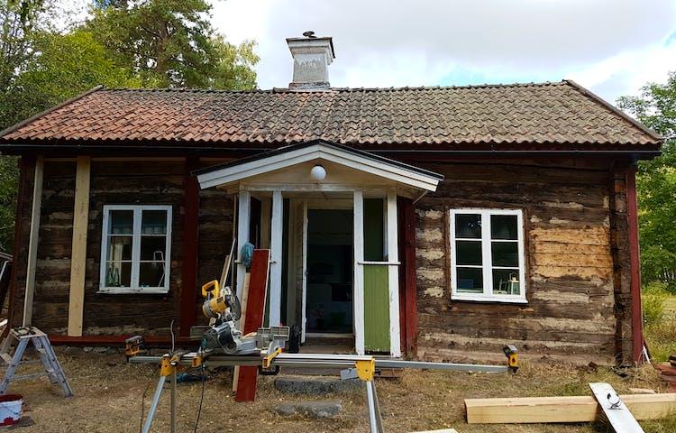 Röd liten träbyggnad. Mitt på långsidan är en liten förstukvist. På vardera sida förstukvisten ett fönster. Vissa plankor i fasaden är omålade.