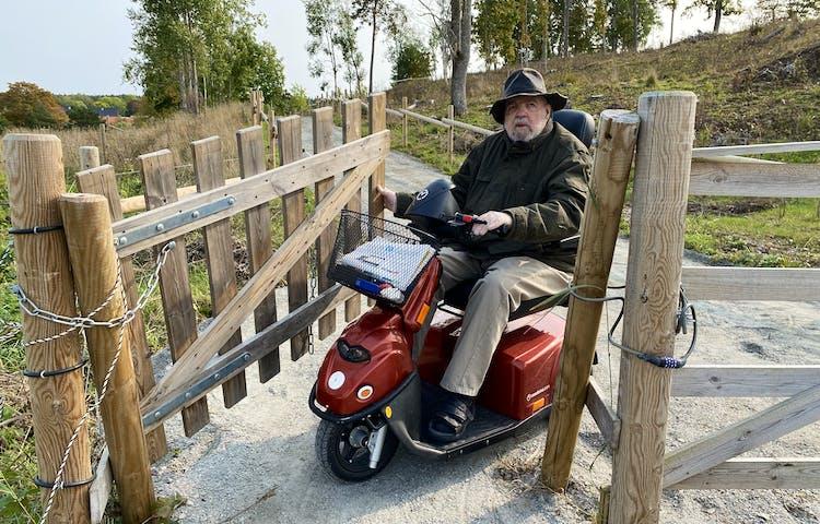 En man i permobil öppnar en trägrind  för att kunna passera igenom. Grinden är bred och marken är jämn och grusad.