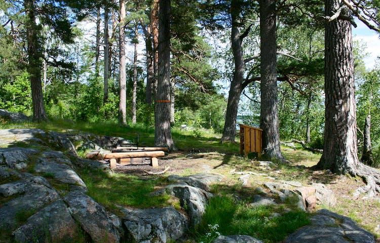 En grillplats med tre stockbänkar och en eldstad står bland klippor. Ett vedförråd still intill grillplatsen.