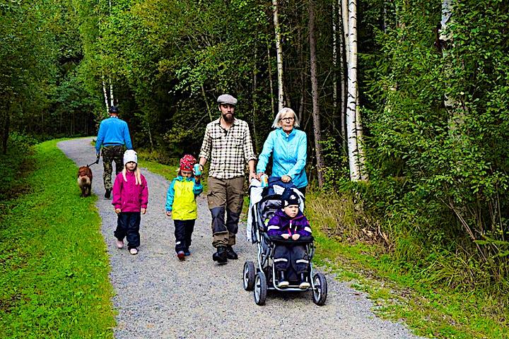 En familj med barn i barnvagn går längs stigen