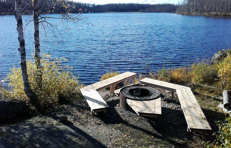 Eldstad med bänkar precis intill vatten.